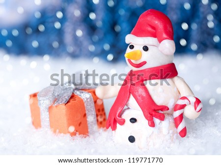 Christmas snowman with gift box  at wintertime