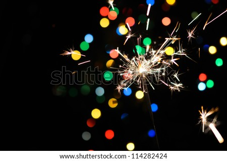 Christmas sparkler and background of colorful bokeh