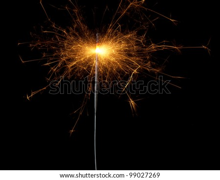 Christmas sparkler isolated on black background. Bengal fire
