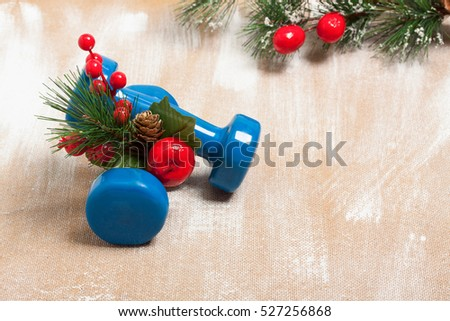 Christmas sport composition with dumbbells, red berries and \ spruce on plywood background. Concept Christmas special for healthy \ lifestyle and sport.