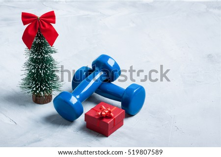 Christmas sport composition with dumbbells, red gift box and  christmas tree with red bow \ on gray concrete background. Concept C�hristmas special for healthy lifestyle and sport.