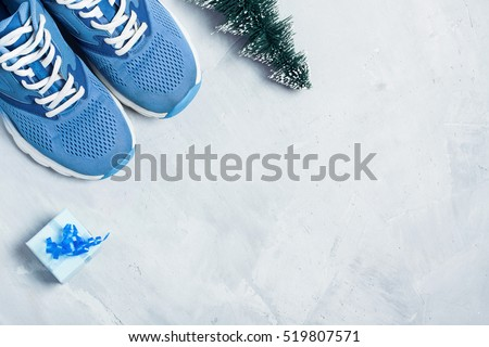 Christmas sport flat lay composition with shoes, christmas tree and blue gift box on gray \ concrete background. Concept C�hristmas special for healthy lifestyle and sport.