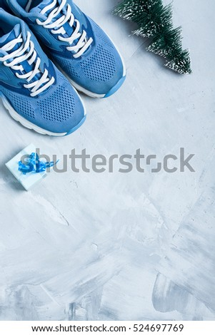 Christmas sport flat lay composition with shoes, christmas tree and blue gift box on gray concrete background. Concept christmas special for healthy lifestyle and sport. Vertical orientation