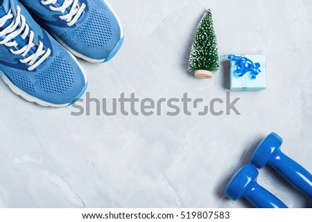 Christmas sport flat lay composition with shoes, dumbbells, christmas tree and blue gift \ box on gray concrete background. Concept C�hristmas special for healthy lifestyle and \ sport.