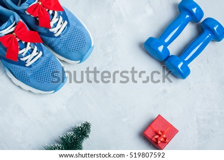 Christmas sport flat lay composition with shoes, dumbbells, christmas tree and red gift \ box on gray concrete background. Concept C�hristmas special for healthy lifestyle and \ sport.