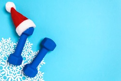 Christmas sport flat lay with dumbbells in red Santa's hat on blue background. Christmas and new year holiday concept for fitness, workout and healthy lifestyle. New year resolution to exercise more.