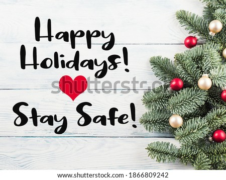 Photo of  Christmas spruce branches with red golden decor on wooden table. Greeting card in times of covid pandemic with text Happy holidays, stay safe