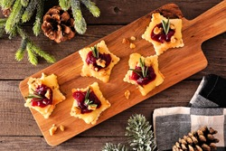 Christmas star shaped appetizers with cranberries and baked brie. Overhead view on a serving board against a wood background.