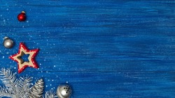 christmas star with balls, silver jingle bell and fir tree branch on blue wooden planks. festive christmas decorations.