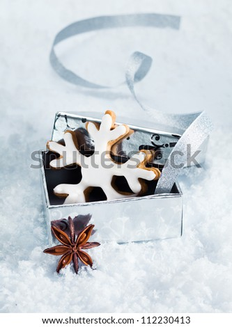 Christmas still life with a Christmas snowflake cookie in a silver gift box nestling in fresh snow