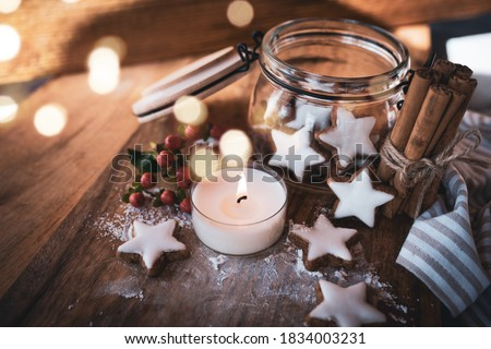 Photo of  Christmas still life with cinnamon stars, baking ingredients. and candlelight on a wooden background with atmospheric bokeh. Short depth of field and space for text.