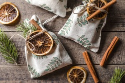 Christmas still life with eco friendly textile gift packaging. Fabric gift pouches decorated by fir tree, dry citrus and cinnamon stick's.