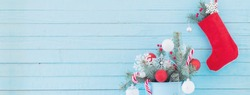 Christmas stocking and fir branches in blue bucket on blue wooden background