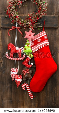 christmas stocking and handmade toys hanging over rustic wooden background vintage style home interior decoration