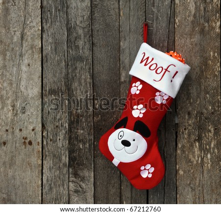 Christmas stocking for a puppy hangs on a rustic wooden wall with copy space.
