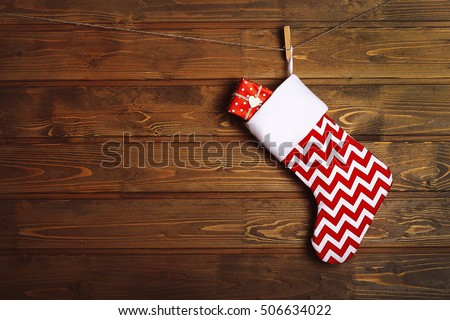 Christmas stocking hanging against wooden wall - Shutterstock ID 506634022