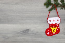 Christmas stocking hanging on pine brach on grey wooden background. Christmas idea decor, copy space