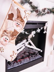 Christmas stocking over fireplace decor, New Year's card scenery. Snowman and stars. New Year concept.