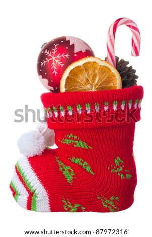 Christmas stocking stuffed with ball, orange and a candy, isolated on a white background