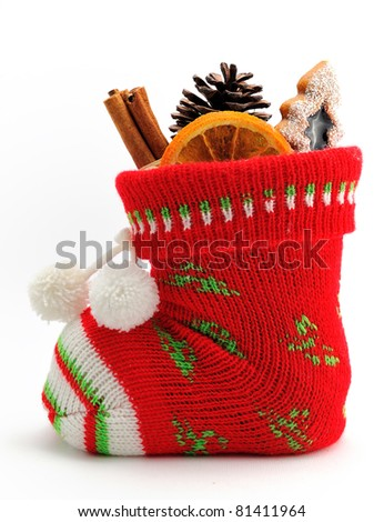Christmas stocking stuffed with candy, fruit, cinnamon sticks and cone isolated on white background