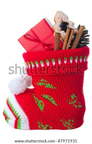 Christmas stocking stuffed with present box, cinnamon sticks and a cookie, isolated on a white background