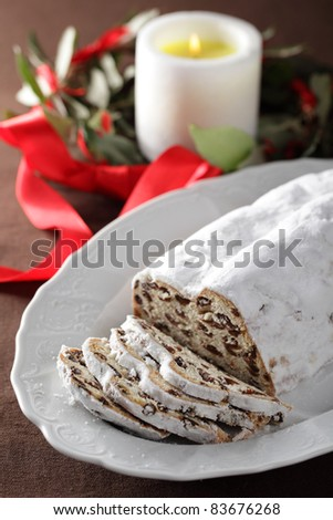 Christmas stollen with raisins against Christmas wreath and candle