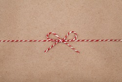 Christmas string or twine tied in a bow on kraft paper background