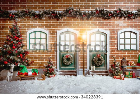 Christmas studio interior decorations with two wooden doors, street light, christmas tree, presents, brick wall, and windows.  #340228391
