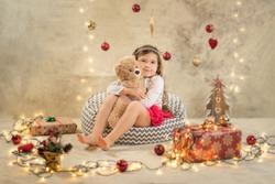 Christmas studio shoot of a cute baby girl that is hugging a teddy bear. Festive, beige background with gifts, Christmas balls and lights