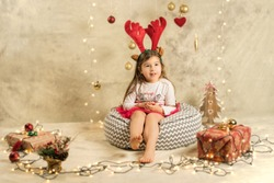 Christmas studio shoot of a cute baby girl wearing reindeer headband. Festive, beige background with gifts, Christmas balls and lights