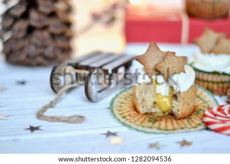 Christmas style decorated picture of a cupcakes on a sled decorated with ginger cookies in a shape of stars on a white background with lights on it. Some cupcakes are in cut, filled with lemon curd