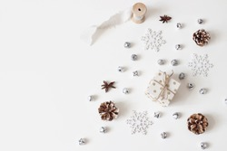 Christmas styled stock composition. Glittering silver jingle bells, snowflakes, pine cones, silk ribbon and anise stars isolated on white table background.Flat lay, top view. Winter decorative pattern