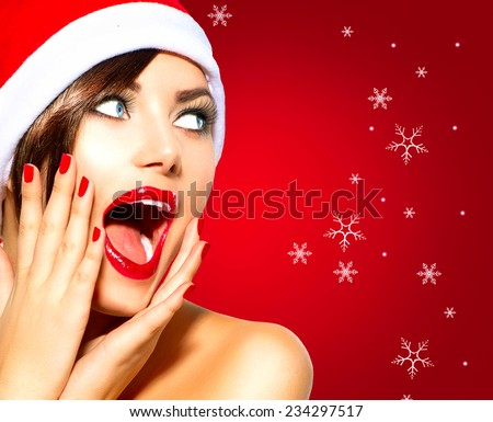 Christmas Surprised Winter Woman. Beauty Model Girl in Santa Hat over holiday red Background. Funny Laughing Woman Portrait. Open Mouth. True Emotions. Red Lips and Manicure. Beautiful Holiday Makeup