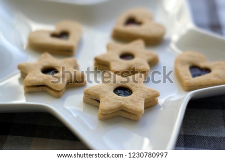 Christmas sweets and cookies made from shortcrust pastry, various shapes filled with marmalade and decorated with chocolate, star shaped plate #1230780997