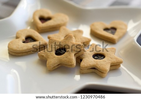 Christmas sweets and cookies made from shortcrust pastry, various shapes filled with marmalade and decorated with chocolate, star shaped plate #1230970486