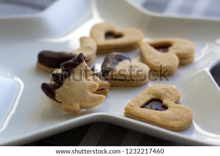 Christmas sweets and cookies made from shortcrust pastry, various shapes filled with marmalade and decorated with chocolate, star shaped plate #1232217460