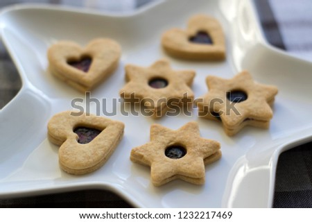 Christmas sweets and cookies made from shortcrust pastry, various shapes filled with marmalade and decorated with chocolate, star shaped plate #1232217469