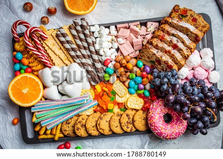 Christmas sweets platter. Christmas fruit cake, candy, chocolate, candy cane, cookies, fruit on black tray. Christmas food concept. Foto stock ©