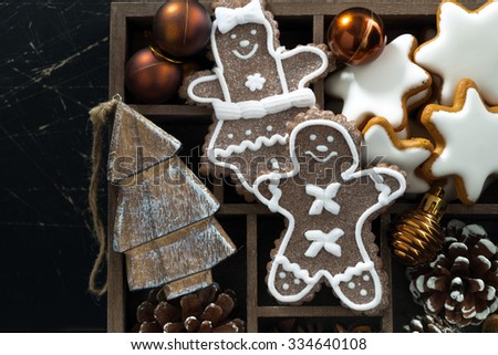 Christmas symbols in a wooden box on black wooden background, closeup, horizontal #334640108