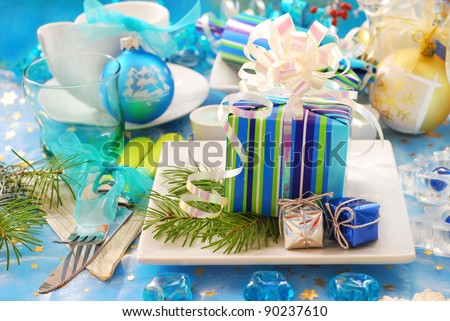 christmas table decoration with gift box on the plate in blue and white color