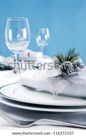Christmas table place plate setting decoration with shiny pinecone in cool silver blue icy theme