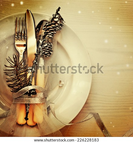 Christmas table place setting with christmas pine branches and plate, kine, fork ,ribbon and bow/ Christmas holidays background