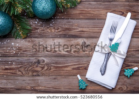 Christmas table place setting with fork and knife, decorated ribbon and bow with fir-tree toys, white napkin and christmas pine branches with christmas balls. Christmas holidays background.