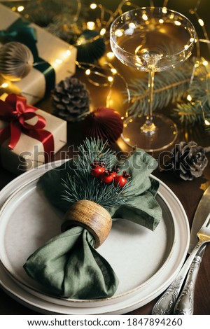 Christmas table setting among gift boxes and garland lights on wooden table. Concept of Christmas and New Year dinner. Photo stock ©