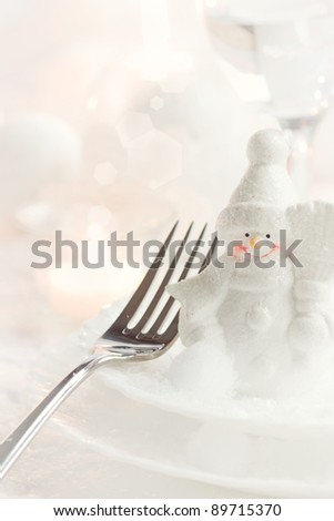 Christmas table setting. Fork and knife in elegant holiday setting with snow and white ornaments