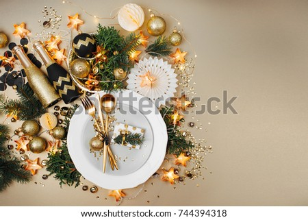 Christmas table setting. Gold and black decoration with fir-tree branch. Flat lay, top view.