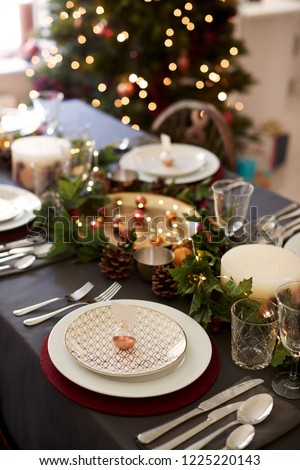 Christmas table setting with bauble name card holder arranged on a plate and green and red table decorations, Christmas tree in the background, elevated view