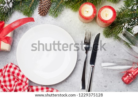 Christmas table setting with candles, champagne, gift box and fir tree branch covered by snow on stone background. Top view with space for your greetings #1229375128