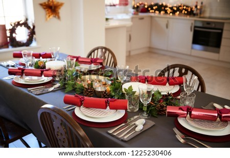 Christmas table setting with Christmas crackers arranged on plates in a dining room, with kitchen in the background