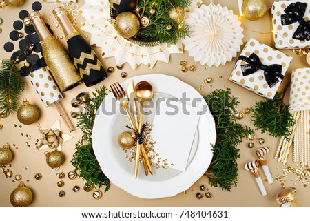 Christmas table setting with Empty card mockup for your text. Gold and black decoration with fir-tree branch. Flat lay, top view.